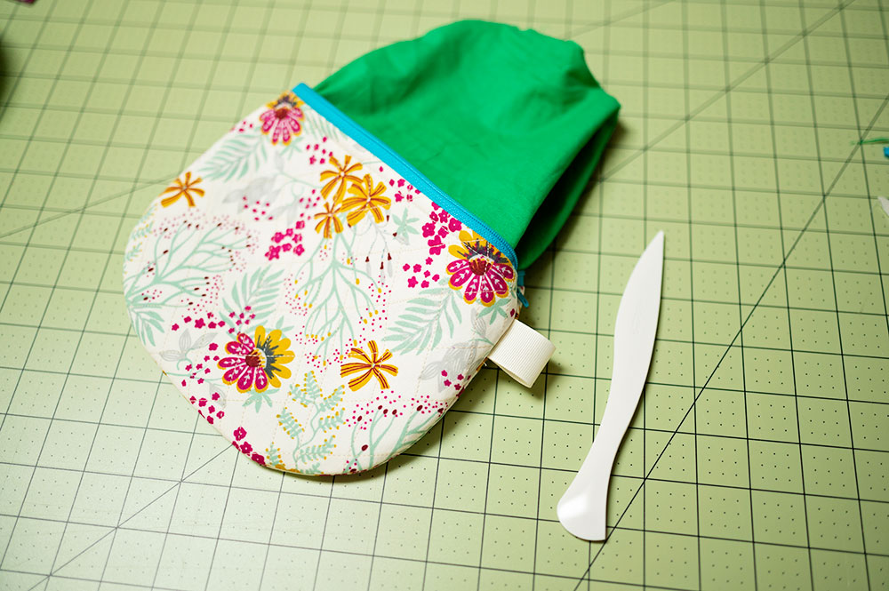 quilted zipper pouch is sewn and turned right side out. Laying on a cutting mat and shown with the point turner tool