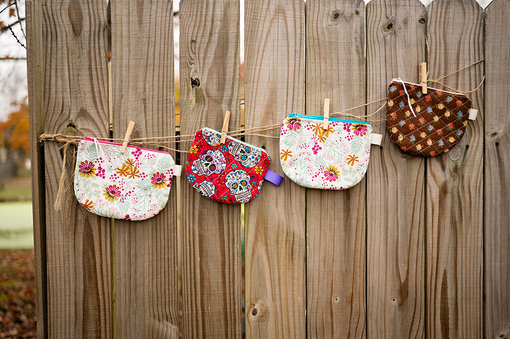 colorful zipper pouches hanging on a line against a rustic fence