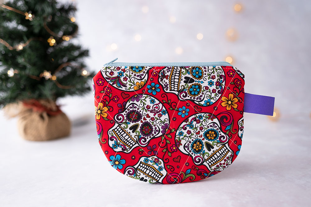 a small red quilted zipper pouch with sugar skulls and a purple tab
