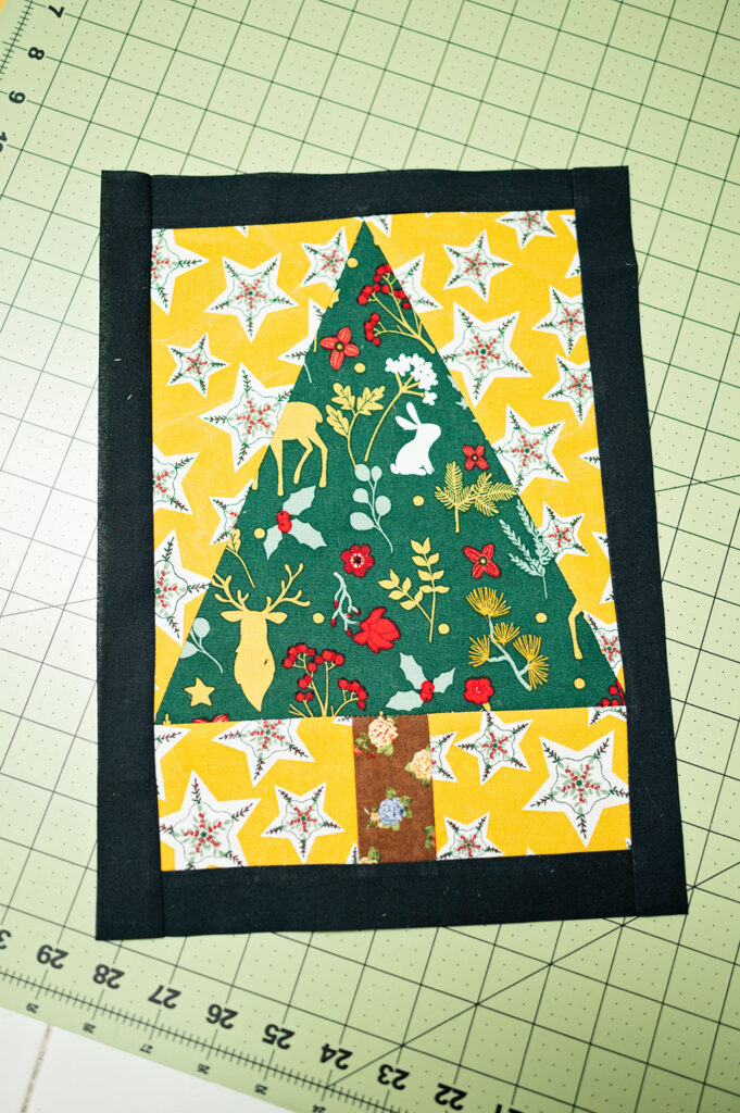 Christmas Tree quilt block with a narrow border sewn into place and trimmed