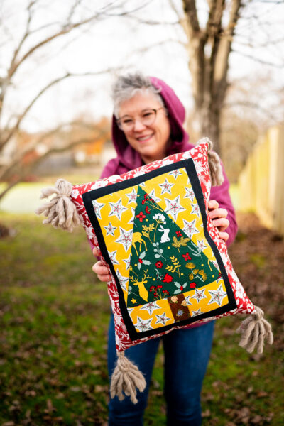 smiling woman holds a complete Christmas tree quilt block sewn into a pillow