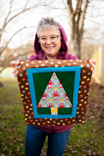 smiling woman holds a complete Christmas tree quilt block