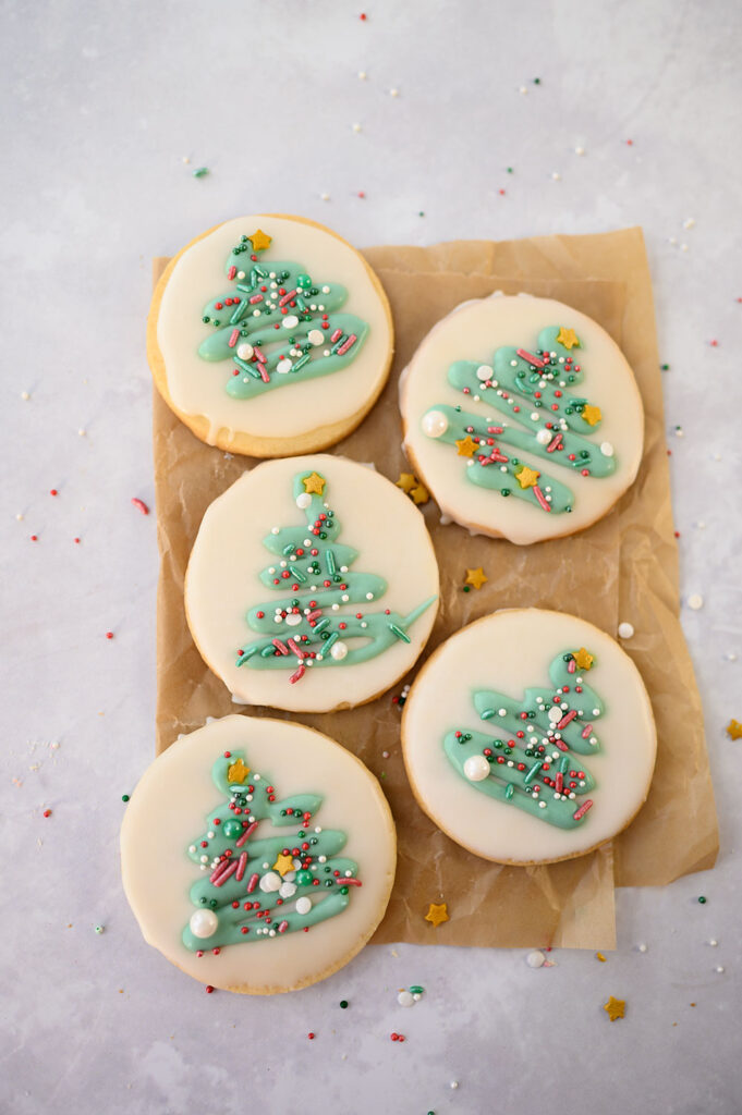 overhead view of 4 round Christmas cookies decorated with green trees and seasonal sprinkles