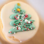 Closeup view of a round Christmas cookie decorated with a Christmas tree and sprinkles