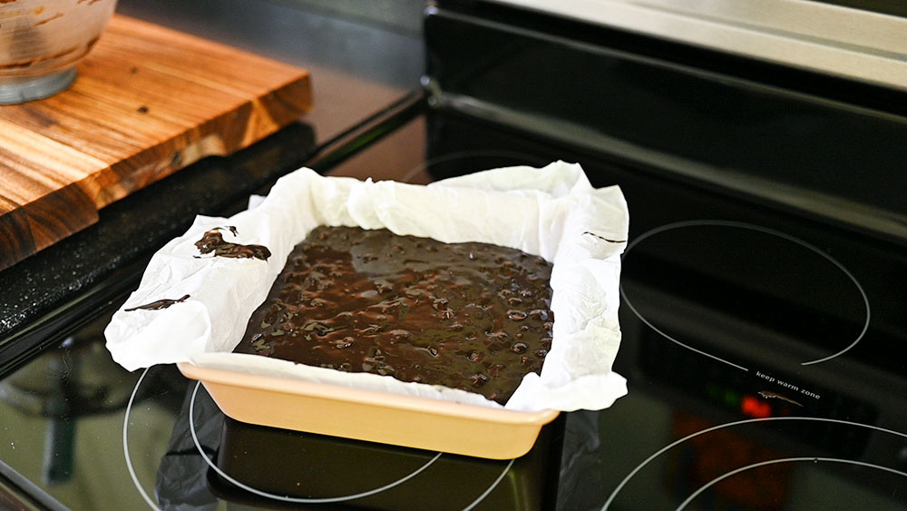 a parchment lined pan is filled with brownie batter and ready to be baked
