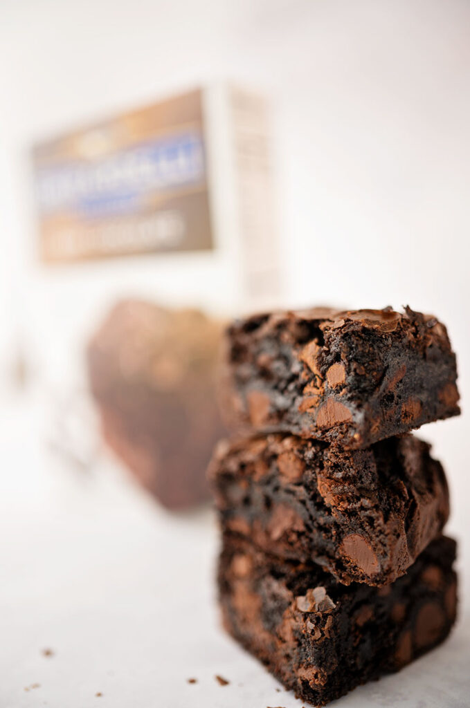 A stack of 3 thick chocolate brownies in front of the mix that made them