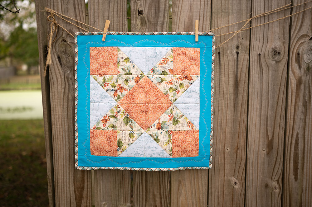 a mini quilt sewn in the ribbon star block pattern
