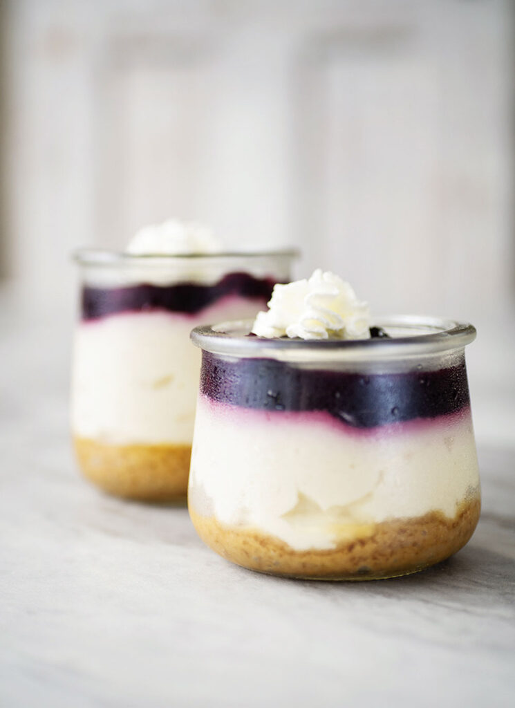 closeup of 2 small glass jar reveals 3 layers of dessert. A graham cracker base, creamy cheescake and a blue berry topping