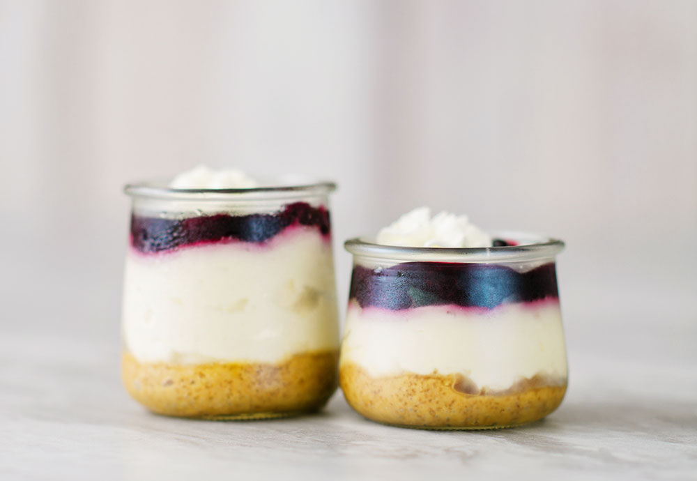 2 small glass jar reveals 3 layers of dessert. A graham cracker base, creamy cheescake and a blue berry topping