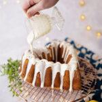 hand pours a thick, white glaze over a heart shaped cake