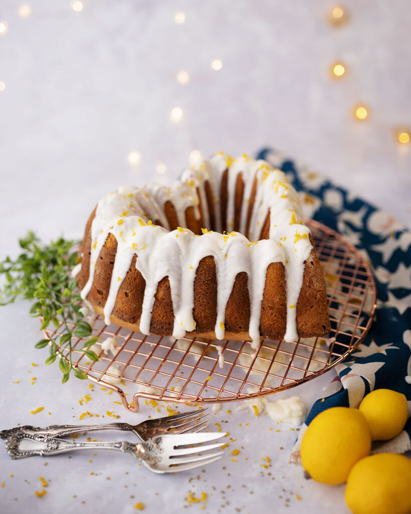 lemon bundt® cake with glaze posed with meyers lemons and antique silver ware