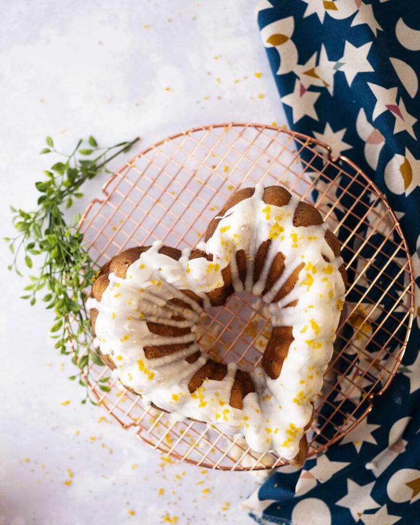 overhead view of a cake shaped like a heart with a white glaze and lemon zest decoration