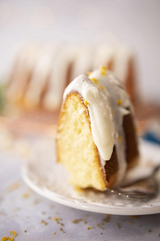 single slice of vanilla cake topped with white glaze and lemon zest