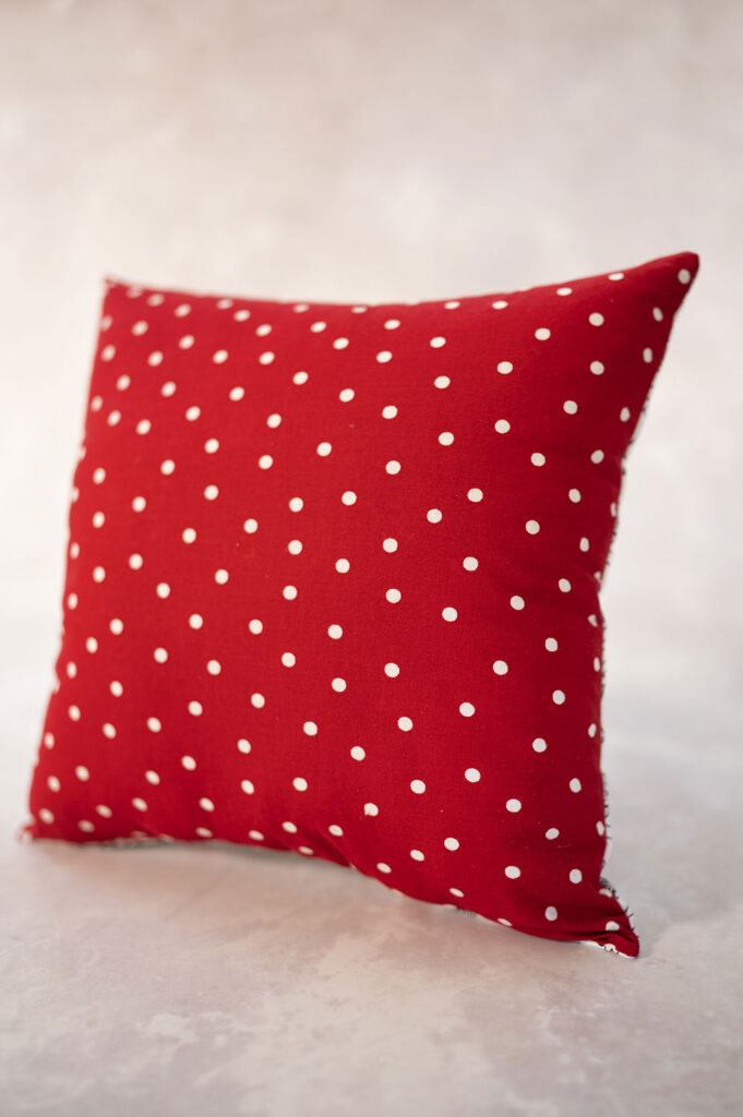 a pillow made with bright red fabric with white polka dots