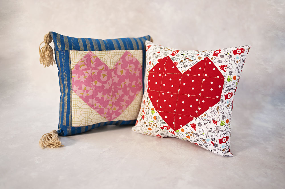 two colorful pillows with a large heart emblem on each