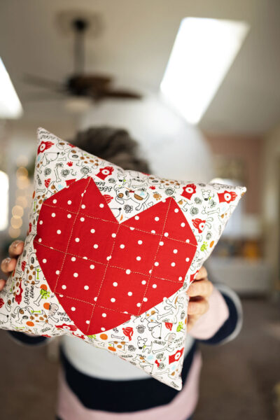 someone is holding a quilted heart pillow in front of them clos to the camera