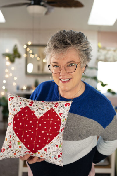 Smiling woman holds a quilted heart pillow