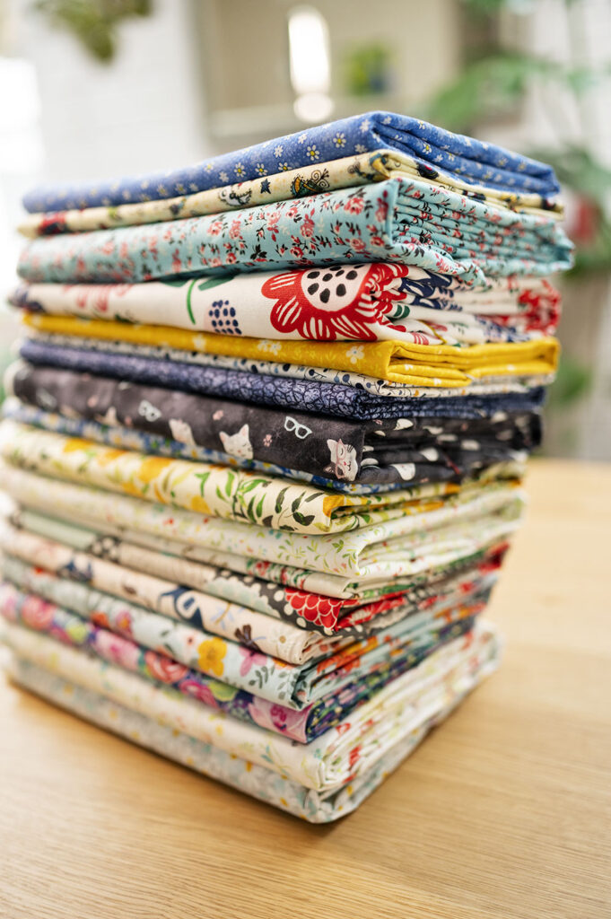 a tall stack of neatly folded fabrics on a wood countertop