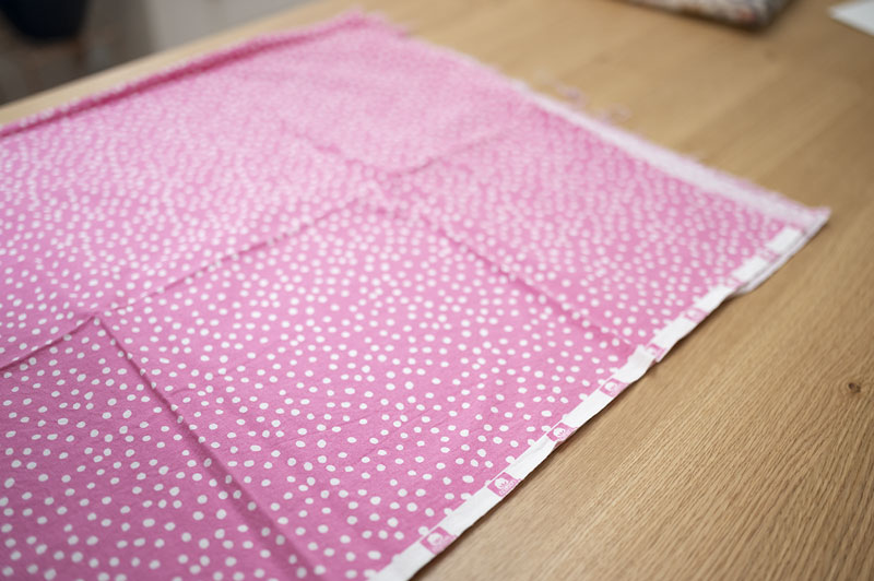 a large cut of pink polka dot fabric laying flat