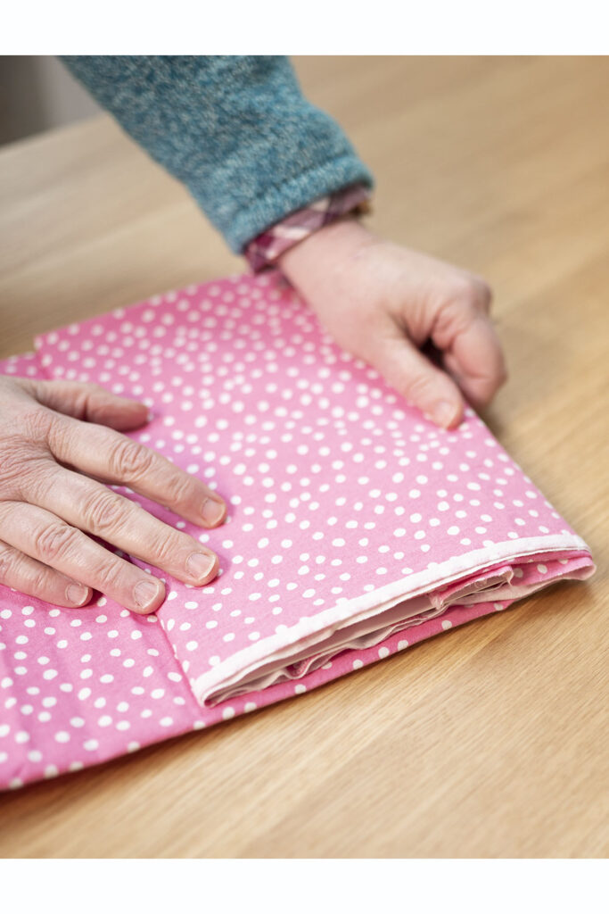 two hands on a cut of pink polka dot fabric
