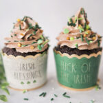 Two chocolate cupcakes in Irish themed cupcake wrappers piped with mile high mocha frosting and shamrock sprinkles