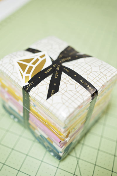 a wrapped fat quarter bundle by Ruby Star Society on a green cutting mat