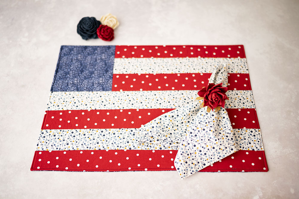a quilted placemat made to look like an American flag with a matching cloth napkin