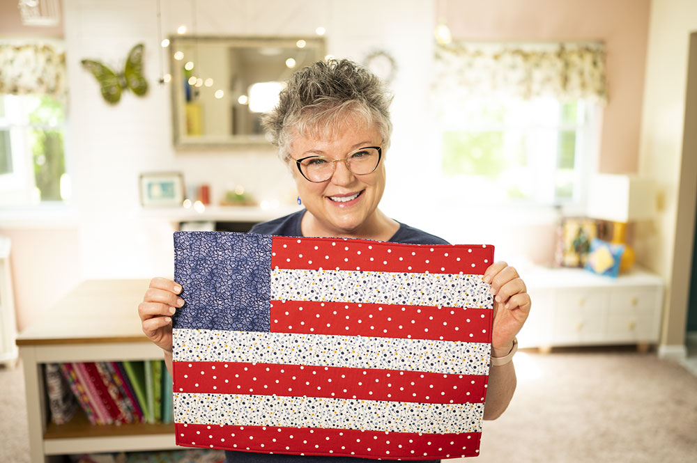 smiling woman holds an placemat that looks like an American Flag