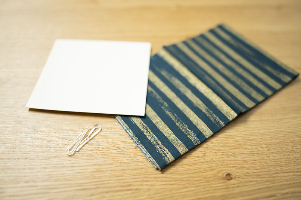 a piece of cardstock, a plastic clip and a small cut of blue rainbow fabric