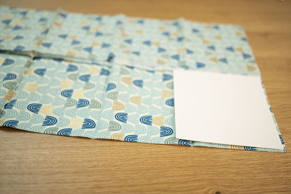 piece of fabric with a square piece of card stock in the lower right corner
