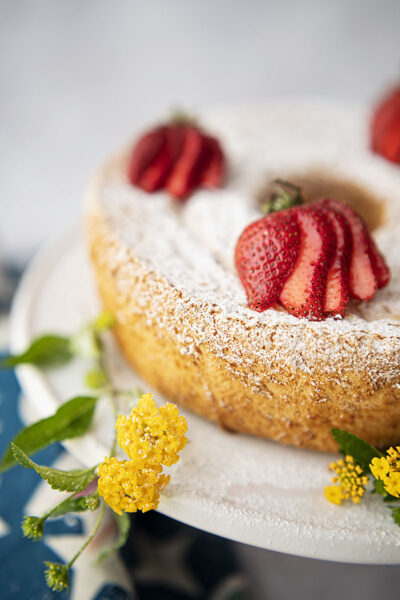 an angel food cake topped with powdered sugar and sliced strawberries with fresh picked yellow flowers