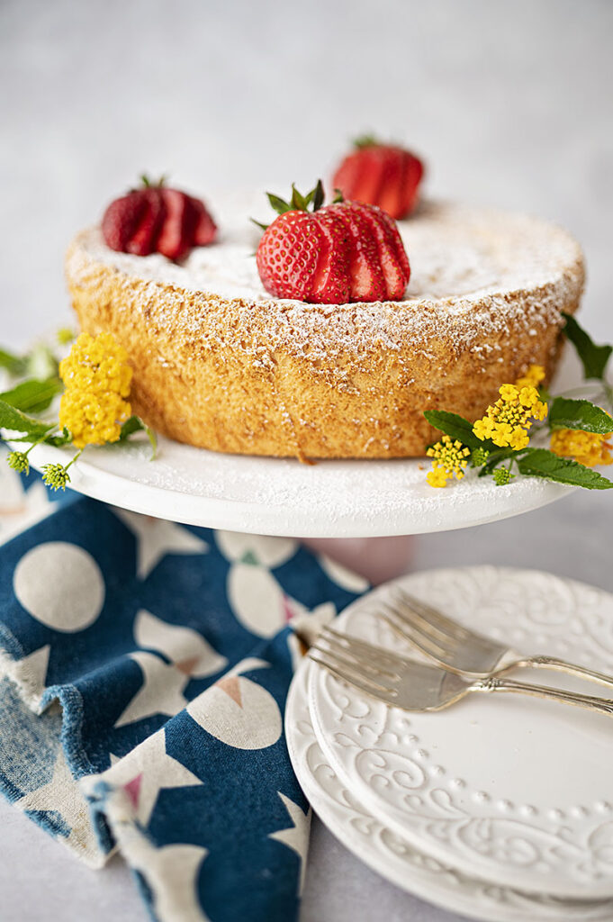 An angel food cake on a cake plate topped with fresh sliced strawberries and decorated with delicate yellow flowers