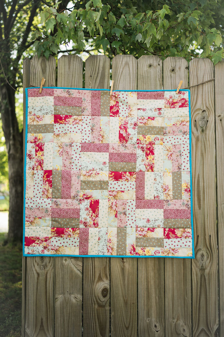 a square patchwork quilt hanging on a rustic fence