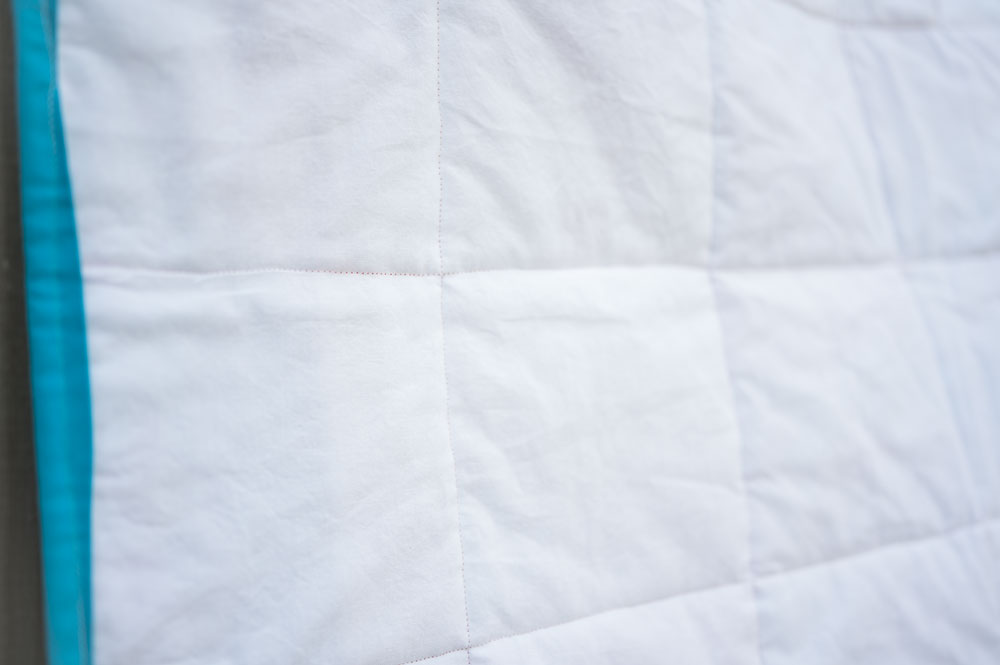 close up of The back side of a baby quilt showing the quilt stitching