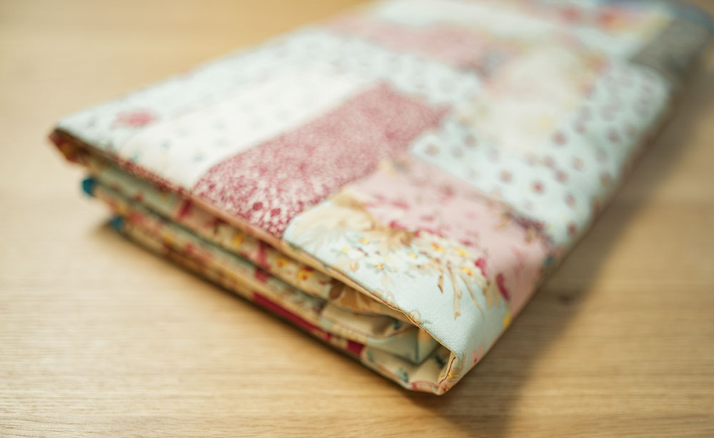 a patchwork quilt is folded flat