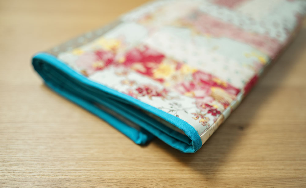 a patchwork quilt with blue binding is folded flat.