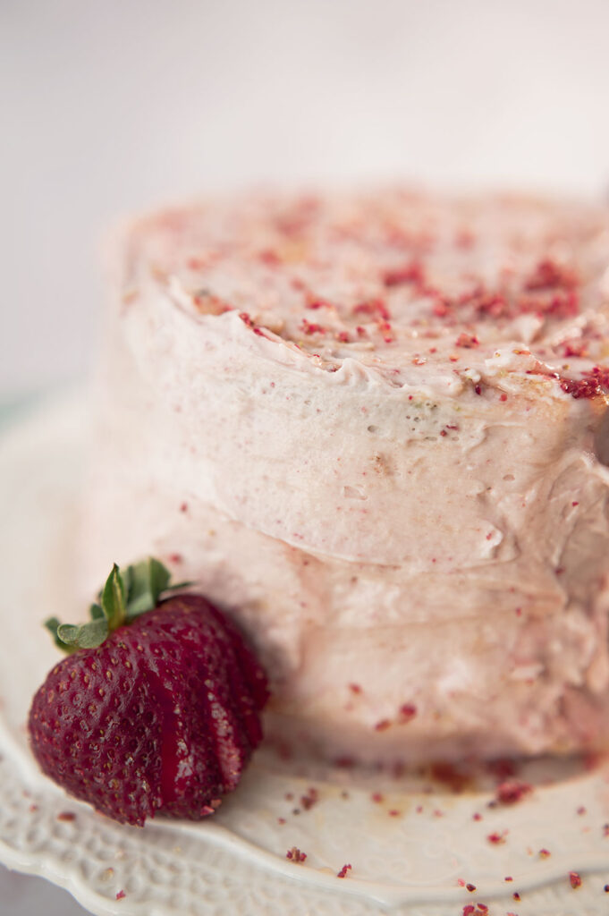 a pink frosted cake on a lacy white cake plate with fresh strawberries