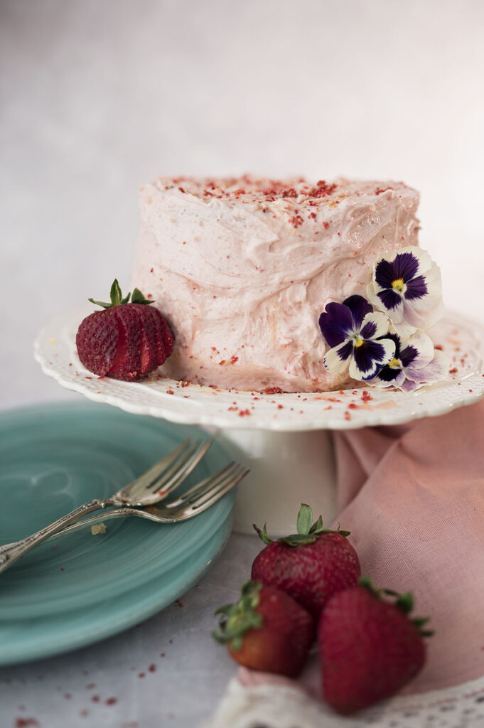 a pink strawberry cake decorated with strawberries and petunias